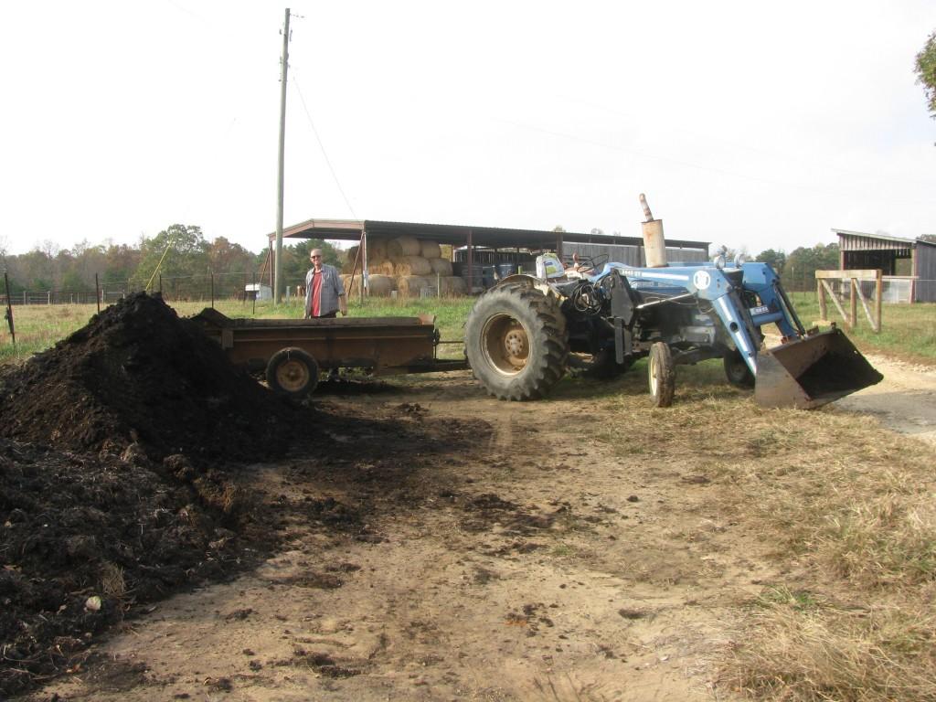 Loading manure onto compost pile